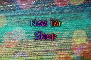 Neu im Shop, im Hintergrund handgesponnenes Garn in einem Farbverlauf von grün nach braun
