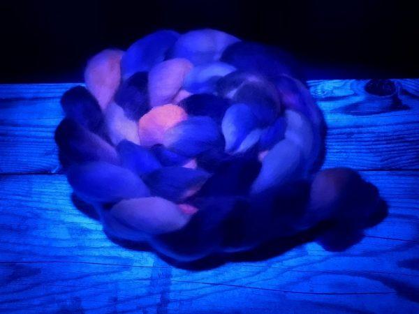 Kammzug aus Teewaterschurwolle in neon pink mit Schwarz und violett unter UV Licht