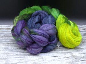 Kammzug aus einer Mischung von Babykamel und Merino im Farbverlauf von hellgrün über grasgrün und lila nach blau