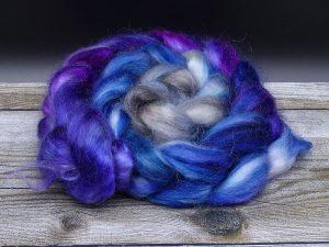 Kammzug aus Mohairfasern in einem Farbverlauf von lila über blau nach grau