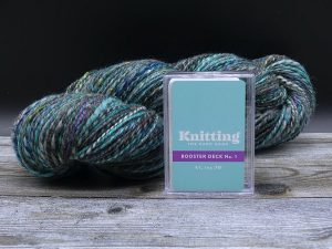 Booster Deck von Knitting the Card Game im Hintergrund ein Strang Garn