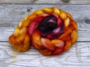 Kammzug aus Mohairfasern in einem Farbverlauf von bordeaux über rot nach orangegelb