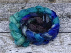 Kammzug aus Mohairfasern in einem Farbverlauf von türkis über blau zu sehr dunklem altrosa